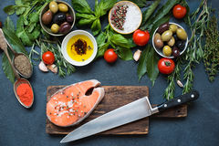 Fresh raw salmon steaks with herbs. High Angle View of Fresh Raw Salmon Steaks on wooden cutting board with rosemary, spices and herbs Royalty Free Stock Photography
