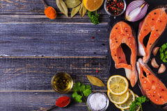 Fresh raw salmon steaks with ingredients. Fresh raw salmon steaks with ingredients on dark background, top view Stock Photography