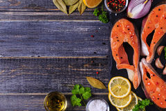 Fresh raw salmon steaks with ingredients. Fresh raw salmon steaks with ingredients on dark background, top view Royalty Free Stock Image