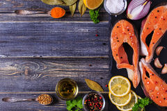 Fresh raw salmon steaks with ingredients. Fresh raw salmon steaks with ingredients on dark background, top view Royalty Free Stock Photos