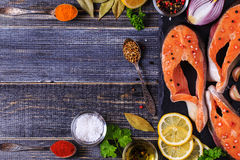 Fresh raw salmon steaks with ingredients. Fresh raw salmon steaks with ingredients on dark background, top view Royalty Free Stock Images