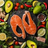 Fresh raw salmon steaks with ingredients, spices and herbs on bl. Ack background. Food concept,  top view, square image Stock Photo