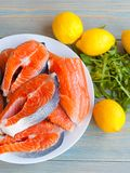 Fresh raw salmon steaks with lemon. And arugula on the rustic table.Top view Royalty Free Stock Photo