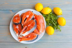 Fresh raw salmon steaks with lemon. And arugula on the rustic table.Top view Stock Image