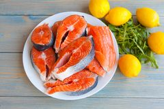 Fresh raw salmon steaks with lemon. And arugula on the rustic table.Top view Stock Photos