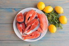 Fresh raw salmon steaks with lemon. And arugula on the rustic table.Top view Stock Photography