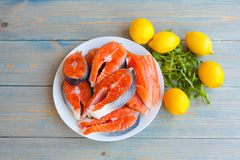 Fresh raw salmon steaks with lemon. And arugula on the rustic table.Top view Stock Photo