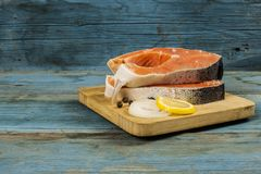 Fresh raw salmon steaks with salt, peppers, lemon. Raw steak of salmon with fresh lemon and pepper peas on the wooden board Stock Photo