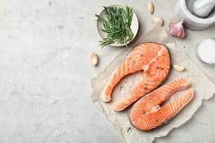 Fresh raw salmon steaks with seasonings. On gray background, top view Royalty Free Stock Photos