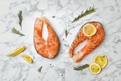 Fresh raw salmon steaks and seasonings. On marble background, top view Stock Photography