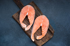 Fresh raw salmon steaks. Top view of two fresh raw salmon steaks on wooden cutting board over dark background Stock Photo