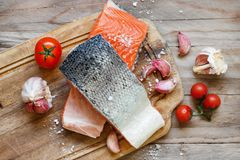 Fresh raw salmon and vegetables. On a wooden cutting board Stock Photos