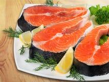 Fresh raw salmon on white plate. Fresh raw salmon green red closeup market Stock Images