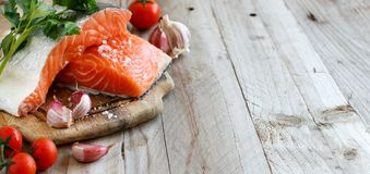 Fresh raw salmon and vegetables. Fresh raw salmon on a wooden cutting board Stock Photo
