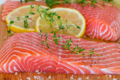 Fresh raw salmon on wooden cutting board. With seasonings Royalty Free Stock Photography