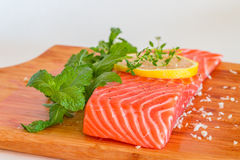 Fresh raw salmon on wooden cutting board. With seasonings Stock Photography