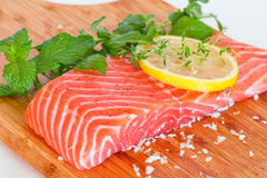 Fresh raw salmon on wooden cutting board. With seasonings Royalty Free Stock Photo