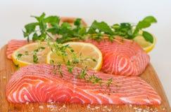 Fresh raw salmon on wooden cutting board. With seasonings Stock Photo