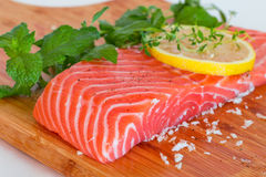 Fresh raw salmon on wooden cutting board. With seasonings Royalty Free Stock Image