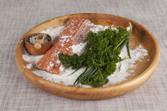 Fresh raw salmon on a wooden tray with parsley and salt Stock Photography