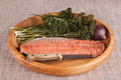 Fresh raw salmon on a wooden tray with parsley and salt Royalty Free Stock Photo
