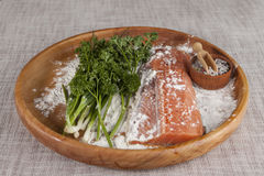 Fresh raw salmon on a wooden tray with parsley and salt Stock Photo