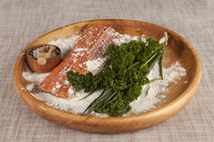 Fresh raw salmon on a wooden tray with parsley and salt. Chilean Fresh raw salmon on a wooden tray with parsley and salt Royalty Free Stock Images