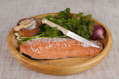 Fresh raw salmon on a wooden tray with parsley, salt and knife. Stock Photos