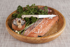 Fresh raw salmon on a wooden tray with parsley, salt and knife. Stock Photo