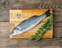 Fresh, raw, saltwater fish, sea bass on a wooden cutting board o. N old wooden aged, rustic table, top view Stock Photo