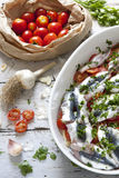 Fresh raw sardines on casserole with cherry tomatoes slices, parsley, garlic and potatoes on rustic mediterranean background Royalty Free Stock Photos