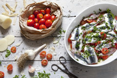 Fresh raw sardines on casserole with cherry tomatoes slices, parsley, garlic and potatoes on rustic mediterranean background Stock Image