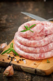 Fresh raw sausage. On the old wooden background Stock Images