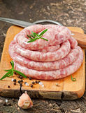 Fresh raw sausage. On the old wooden background Royalty Free Stock Image