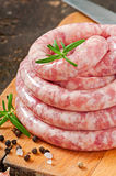 Fresh raw sausage. On the old wooden background Stock Photography