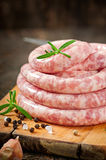 Fresh raw sausage. On the old wooden background Stock Photo