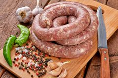 Fresh raw sausage. Ingredient, charcuterie. Fresh raw sausage on the wooden background royalty free stock images