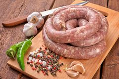Fresh raw sausage. Ingredient, charcuterie. Fresh raw sausage on the wooden background stock image