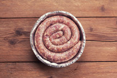 Fresh raw sausage. On wooden background Stock Photos