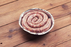 Fresh raw sausage. On wooden background Royalty Free Stock Photos