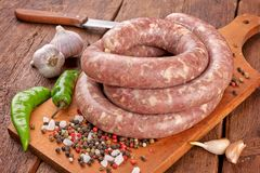 Fresh raw sausage. Ingredient, charcuterie. Fresh raw sausage on the wooden background stock photography