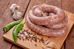 Fresh raw sausage. Ingredient, charcuterie. Fresh raw sausage on the wooden background royalty free stock photography