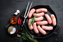 Fresh raw sausages on a cast-iron grill pan on a black background Stock Photo