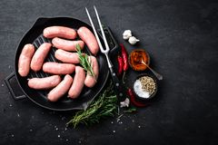 Fresh raw sausages on a cast-iron grill pan on a black background. Top view Stock Photography