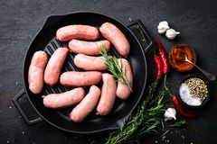 Fresh raw sausages on a cast-iron grill pan on a black background. Top view Stock Photo