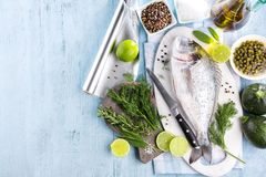 Fresh raw sea bream fish cooking on black stone countertop, top view royalty free stock photo