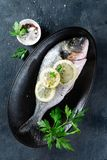 Fresh raw sea bream fish decorated with lemon slices, herbs and parsley on dark background. Healthy food concept, top view, copy stock images