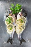 Fresh raw sea bream fish decorated with lemon slices, herbs and parsley on light background. Healthy food concept, top view, copy. Fresh raw sea bream fish stock photos