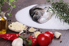 Fresh raw sea bream fish on salt decorated with lemon and herbs on blue wooden background. Healthy food concept Stock Image