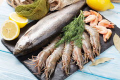 Fresh raw sea food with spices. On stone plate over wooden table background. Top view Royalty Free Stock Images